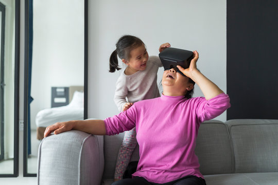 Senior asian woman Using VR glasses indoor with her granddaughte