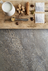Ingredients for spiced chai on wooden plank.