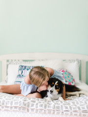 Young girl snuggling with her pet puppy