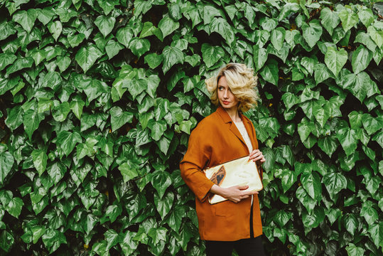 Woman with a clutch standing against ivy wall