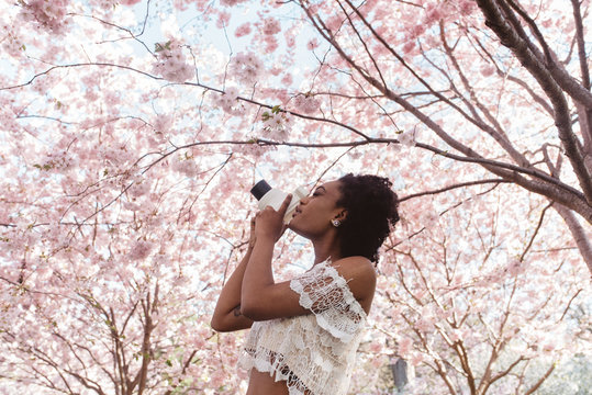 A young black woman in a park filled with cherry blossom trees