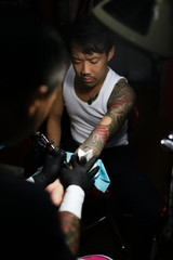 Professional asian tattooer makes a tattoo.
