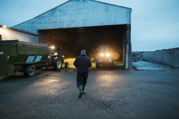 Dairy farmer walking toward tractor
