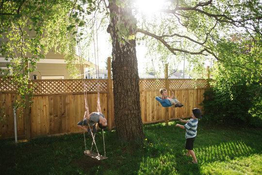 Three boys playing on swings