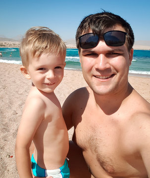 Funny portrait of young father making selfie image with his toddler son the sea beach at bright sunny. Family relaxing and having good time during summer holiday vacation.