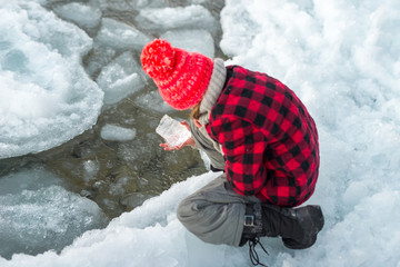 Girl examines ice kneeling by shore of Ontario lake