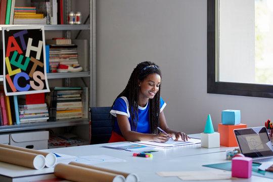 Smiling Female Graphics Designer Working At Desk