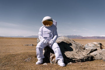 Person in cosmonaut costume sitting on rock