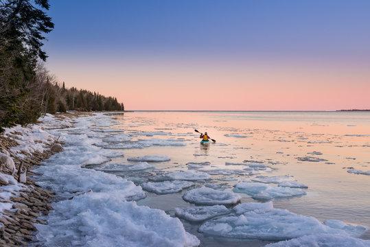 Solitary man kayaks in vast Ontario winter landscape