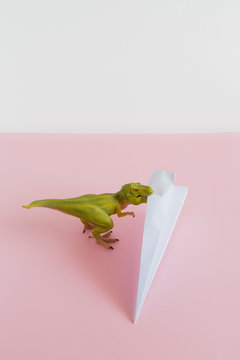 Dinosaur eating a paper airplane. Travel concept.