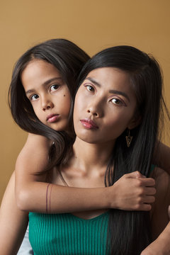 Portrait of mother and daughter embracing indoors