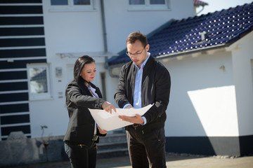 A real estate agent showing a customer house plan in front of the house