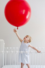 Girl in crib trying to touch red balloon