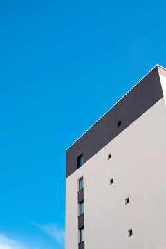 City pattern. Grey and white building facade and blue sky.