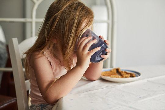 Girl drinking milk at table