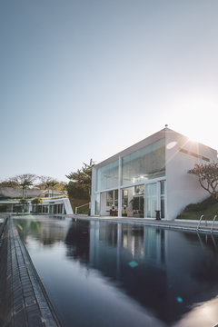 modern luxury villa with huge swimming pool at sunset