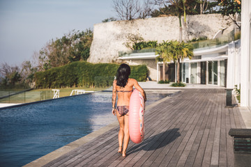 beautiful woman with inflatable pink donut walking along a big swimming pool