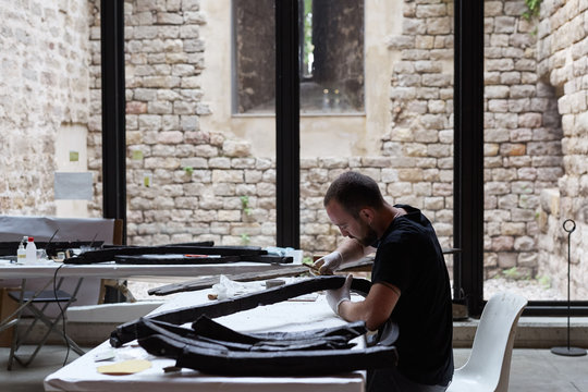 Museum restorer working with old boat pieces
