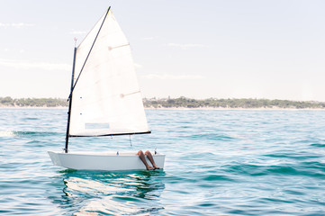Small sail boat on a flat ocean, waiting for wind