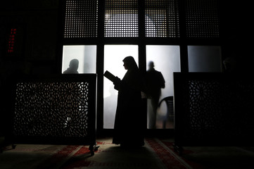 A Palestinian woman reads the Koran in al-Aqsa Mosque, on the compound known to Muslims as al-Haram al-Sharif and to Jews as Temple Mount, during the holy month of Ramadan in Jerusalem's Old City