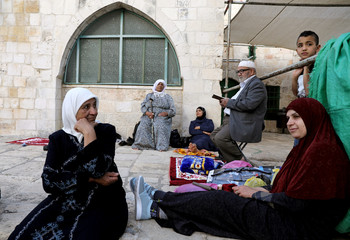 A Palestinian man reads the Koran outside the al-Aqsa mosque,on the compound known to Muslims as al-Haram al-Sharif and to Jews as Temple Mount, during the holy month of Ramadan in Jerusalem's Old City