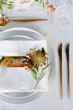 From above an elegant wedding reception tabletop with overgrown greenery, soft copper accents