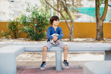 7 year old boy holding a soccer ball outdoors