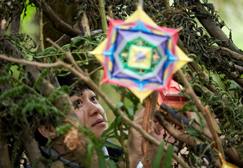 Asian female and her hand-woven dream catcher graphic in a natural wood environment.