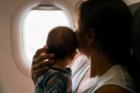 Mother and daughter looking through window in airplane