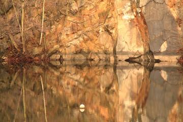 Felswand spiegelt sich symmetrisch in Wasseroberfläche