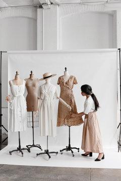 Shop owner dressing mannequins in vintage clothing