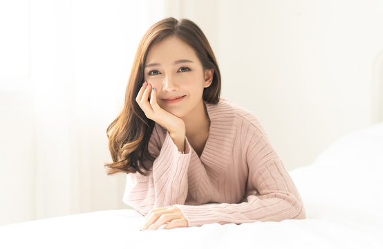 Portrait of young Asian woman smiling friendly and looking at camera in living room.Woman's face closeup. Concept woman lifestyle and winter. Autumn, winter season.