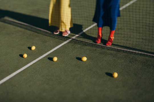 Young girls looking over citrus fruits scattered in tennis court