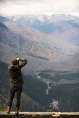 A man takes a photograph with camera at Glacier National Park, Montana
