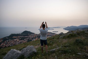A man takes a mobile photo of Dubrovnik, Croatia from above the city.