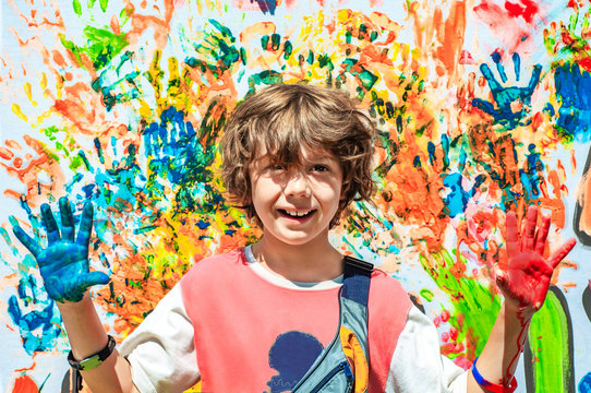 Happy cute boy with painted paint palms outstretched ahead. Happy summer holidays. School education. Children's summer camp outdoors