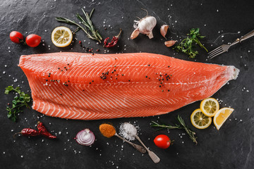 Fresh raw salmon fish steak with spices on dark stone background. Creative layout made of fish, top view, flat lay.