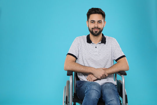 Young man in wheelchair on color background. Space for text