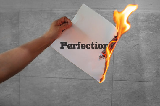Perfection word text burning with fire