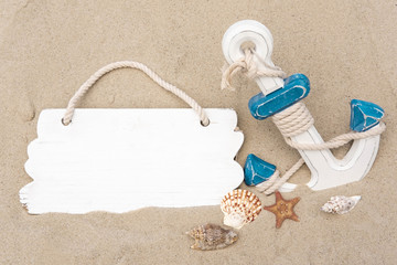 Photo anchors on the sand with a board for the inscription. Template for tourist banner. Holidays at sea, vacation