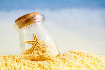 Vacation background with starfish in a glass vessel against the sea, soft focus, copy space