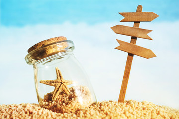 Vacation background with starfish in a glass vessel and a wooden pointer with space for your text against the sea, soft focus