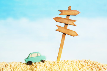 Vacation background with a wooden pointer with space for your text and a small toy car on the background of the sea, soft focus