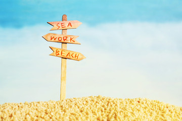 Vacation background with a wooden pointer with the text Sea, Work, Beach against the sea, soft focus