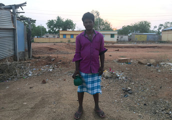 Rajappa, holding a container, poses for a photograph before he walks off to a field to relieve himself in Hirebenakal village