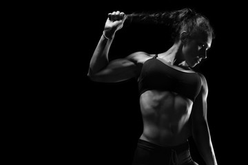 Fit athletic sporty woman posing on black background