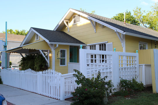 A small cozy house with a white fence and green bushes in the summer, Amelia island, Florida, USA
