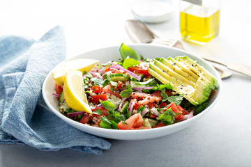 Fresh vegetables and quinoa salad with avocado and lemon dressing