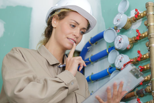 female worker next to water meter with water pipe