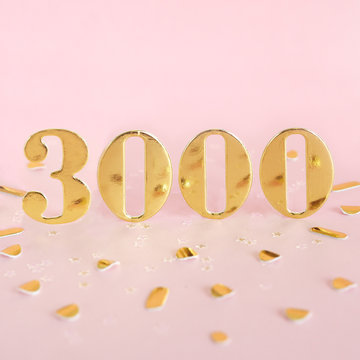 The number 3000 in golden numbers on a pink background and golden confetti. Space for text...